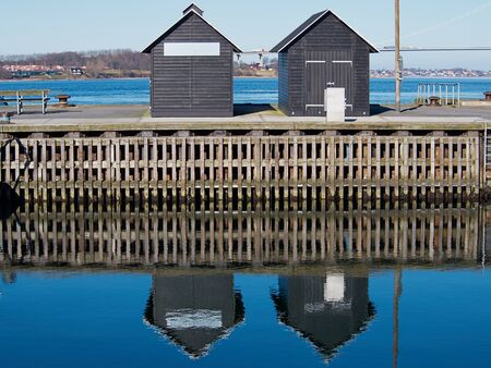 sheds: Blue water ripples background -  Two small wooden sheds reflected in the water