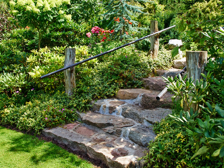 home and garden: Natural stone stairs landscaping in beautiful lush green blooming home garden Stock Photo
