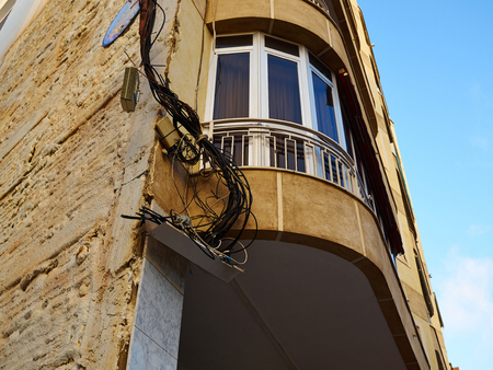 messed: Tangled electric cable mess on a wall of building