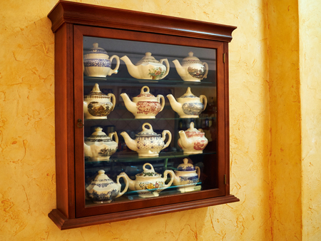 tea hot drink: Collection of decorative classical design tea pot in a wooden display cabinet