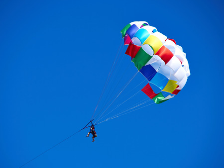 Parasailing with colorful parachute in clear blue sky popular vacation activity in summer resorts 版權商用圖片