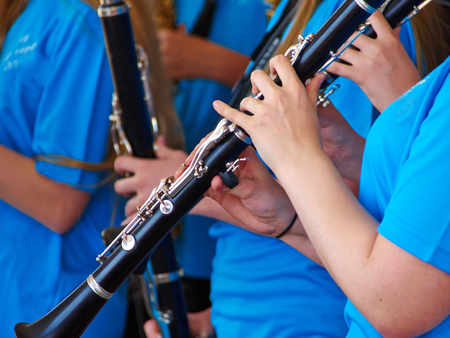 clarinete: Young woman musician playing clarinet as part of a big orchestra