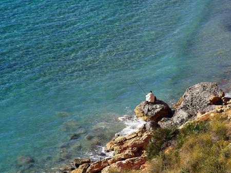 Great leisure activity - Elderly man fishing by the ocean sea in Spain