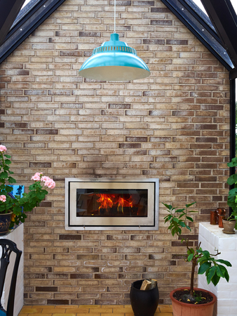 Burning modern trendy design firplace made of steel and glass installed in bricks wall