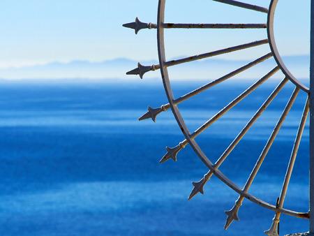 Dekorativer schmiedeeiserner Zaun am blauen Meer Costa Blanca Spanien Sommerurlaub Hintergrund mit Platz für Text und Grafiken