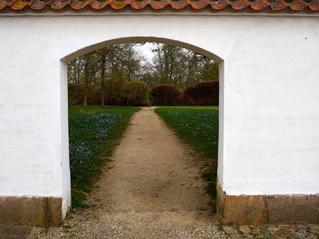 Traditional classical stone arch gate leasing to a beautiful estate garden Denmark