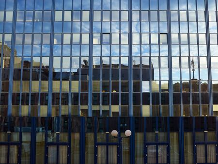 Corporate modern office building with glass windows and reflection of sky 写真素材 - 131843410