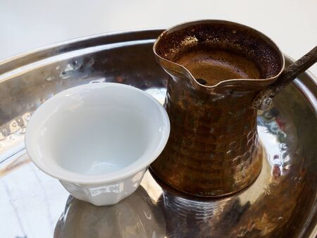 Traditional Turkish Arab Greek coffee served in an old copper cezve