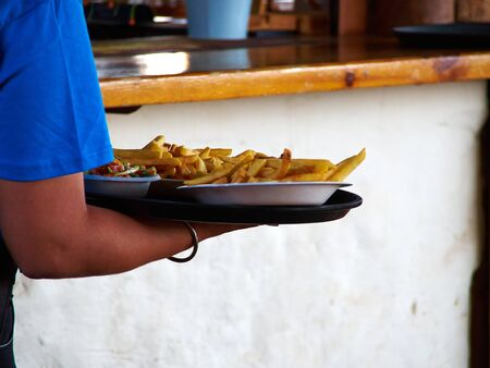Tasty fresh chips French Fries potatoes served to the table Фото со стока