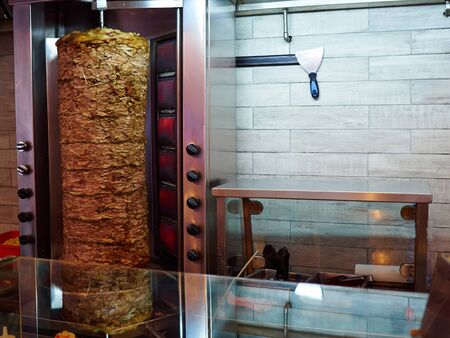 Closeup of Doner Kebab Shawarma Gyros in the making in a restaurant typical Middle East Mediterranean street food