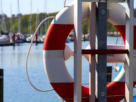 Life buoy ring hanging in a marina with boats in the background as an emergency response and life saving tool