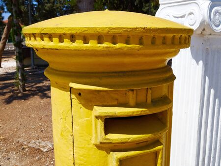 Traditional yellow English style post box mailbox in a street in Paphos Cyprus