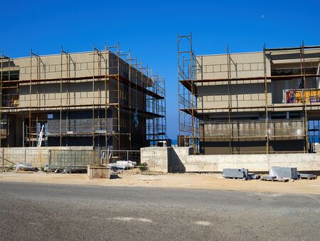 Modern construction site with scaffold platform sytem by the ocean with clear blue sky background