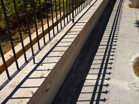 Iron fence and shade of it on a sidewalk in a vanishing point view urban background image