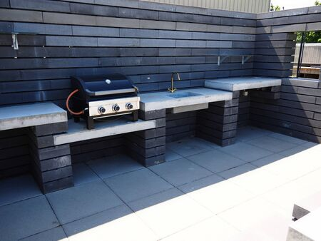 Stylish modern design outdoors garden pation kitchen with gas barbecue and sink made of black and white bricks