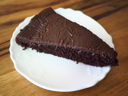 Close up view of a llice of tasty dwlicious Chocolate Cake with Frosting served on a white plate with space for text and graphics Stock fotó