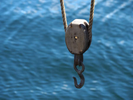 Marine sailing yachting background image of boat pulley with sea water behind and space for text and graphics in the left side