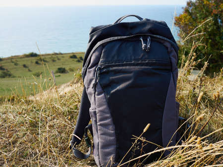 Hiking travel backpack with nature landscape background - great outdoors activity image