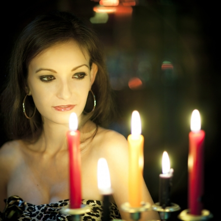 A young woman holding a metal rose in a dark room, just lightened by candles