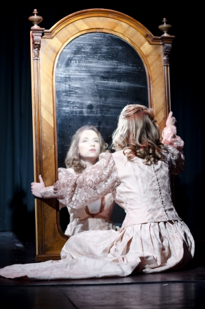 A young girl sitting in front of a big mirror and looking at her own reflection, mirror stage concept shot photo