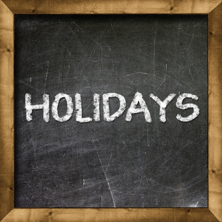 Holidays handwritten with white chalk on a blackboard