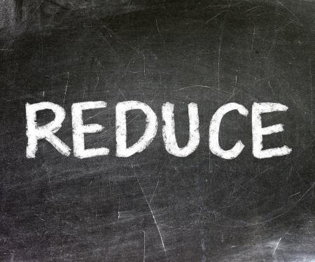 Reduce handwritten with white chalk on a blackboard              photo