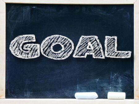 priorities: Goal handwritten with white chalk on a blackboard