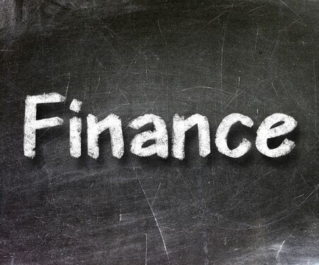 Finance handwritten with white chalk on a blackboard                photo