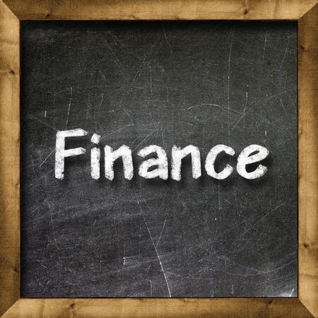 Finance handwritten with white chalk on a blackboard Stock Photo