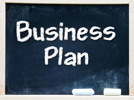 Business Plan handwritten with white chalk on a blackboard                    Stock Photo