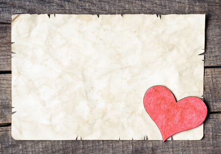 Wooden heart on old paper