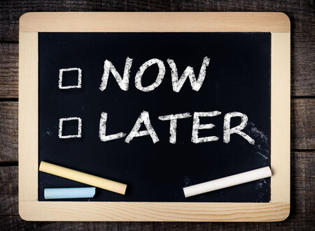 Now and Later Check Boxes on blackboard on wooden background  Stock Photo