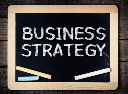Business strategy handwritten with white chalk on a blackboard on wood background