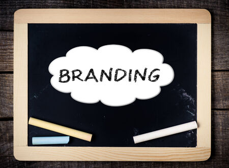 Branding handwritten with white chalk on a blackboard on wood background  Stock Photo