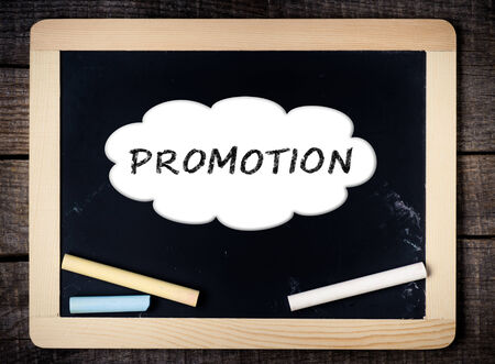 Promotion handwritten with white chalk on a blackboard on wood background  photo