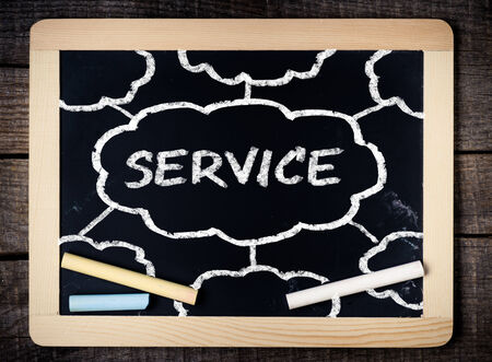 Services title written with chalk on blackboard on wood background