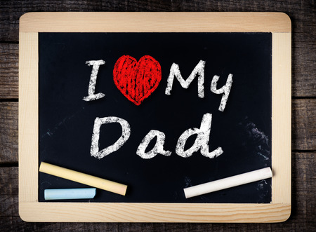 Hand writing I Love my Dad on chalkboard on wood background