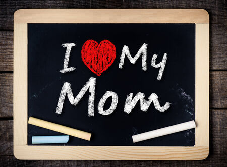 I love my mom phrase handwritten on the school blackboard on wood background  photo