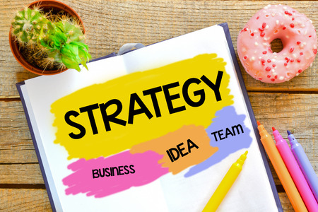Strategy written in the notebook on a wooden background Stock Photo
