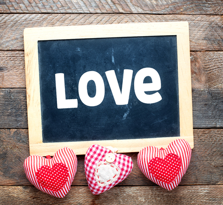 Love text on a chalk board on a wooden background