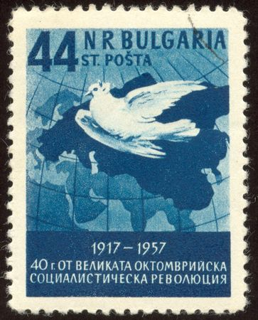 The scanned stamp. The Bulgarian stamp. The pigeon flies over a map. photo