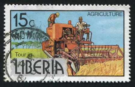 LIBERIA - CIRCA 1976: The combine reaps wheat crop, circa 1976. photo
