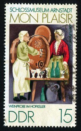 postoffice: GERMANY  - CIRCA 1974: FScenes from 18th century Thurigia, Dolls Village, Arnstadt Castle Museum. Wine tasters,  circa 1974.