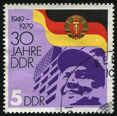 GERMANY- CIRCA 1979: stamp printed by Germany, shows DDR Arms and Flag Worker, circa 1979.