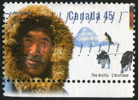 CANADA - CIRCA 1995: stamp printed by Canada, shows Inuk man, igloo, sled dogs, circa 1995 Stock Photo - 9384728