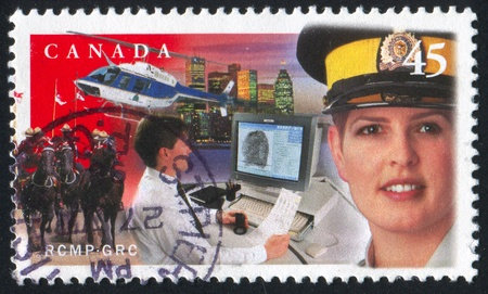 mountie: CANADA - CIRCA 1998: stamp printed by Canada, shows Female mountie, helicopter, cityscape, circa 1998 Editorial