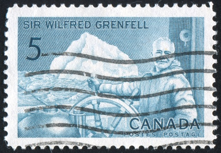 CANADA - CIRCA 1965: stamp printed by Canada, shows Sir Wilfred Grenfell at whell of hospital ship Strathcona II, circa 1965 Stock Photo - 9742651