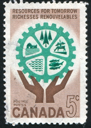 CANADA - CIRCA 1961: stamp printed by Canada, shows Natural Resources and Hands Holding Cogwheel, circa 1961 photo
