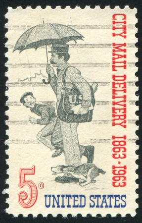 UNITED STATES- CIRCA 1963: stamp printed by United States, shows letter carrier and a boy running after him, circa 1963 Stock Photo - 10373872
