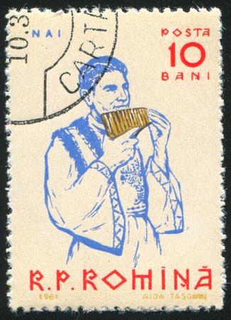 panpipe: ROMANIA - CIRCA 1961: stamp printed by Romania, shows Peasants playing musical instruments, Panpipe, circa 1961 Stock Photo